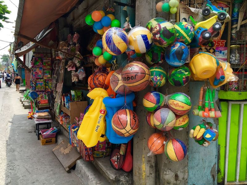 Balls and other toys hang on display at a streetcorner store in Makati, Philippines. Small Business The Shop Around The Corner Streetcorner Balls And Toys Plastic Toys Live Love Shop