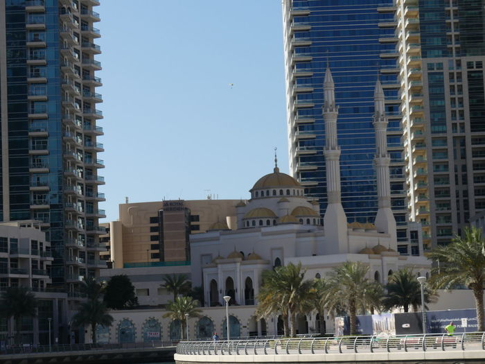 Mosque dwarfed by Skyscrapers at the Marina, Dubai, United Arab Emirates 2019 Dubai UAE 2019 Marina Palm Trees Mosque Islam Religion No People Dome Place Of Worship Spirituality Place Of Worship Shaded Minarets Gold Dome Belief Composition Outdoor Photography Tower Blocks Skyscrapers Hidden City Architecture Arabic Architecture