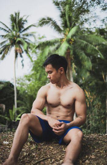 Shirtless muscular man sitting on land