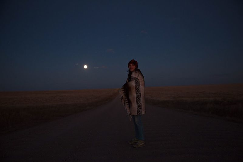Woman wrapped in blanket standing on street amidst field against sky at dusk