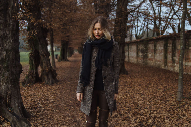 Young woman walking against trees at park