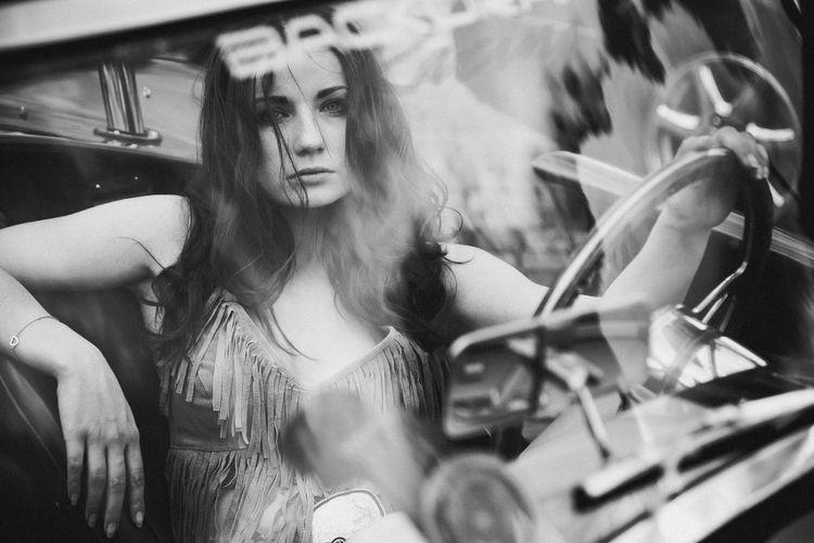 Portrait of beautiful woman sitting in car