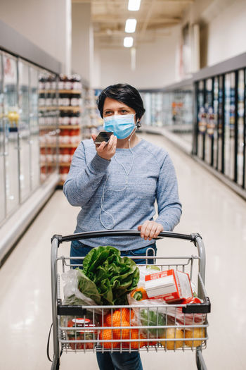 Middle age brunette woman shopping in grocery store supermarket and talking on audio chat phone.