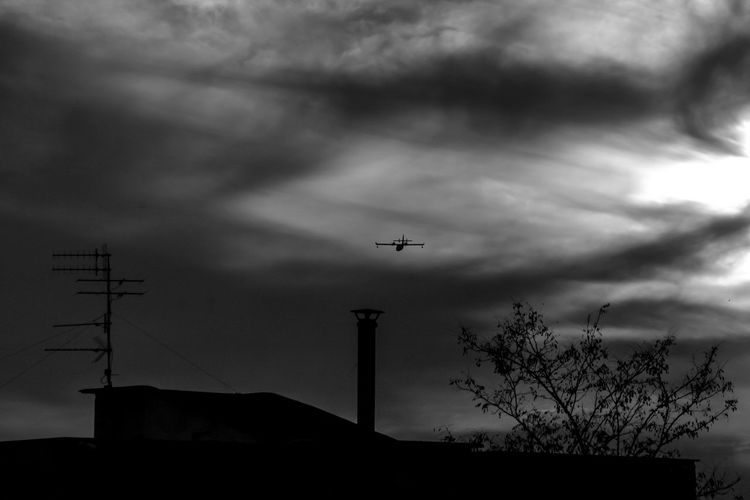 Low angle view of silhouette airplane flying against sky