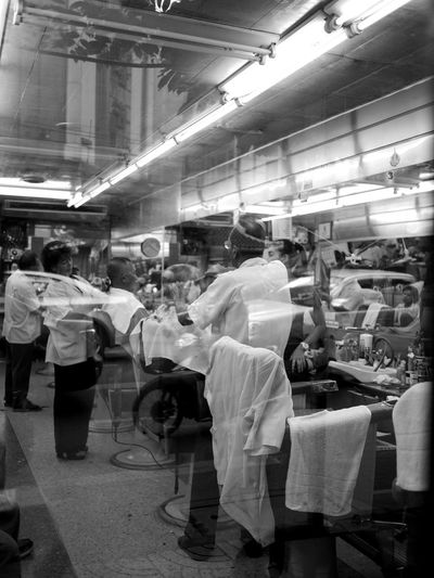 Old classic barber shop at Yaowarat Road in Bangkok, Thailand with street reflected on shop door window Connected By Travel Double Exposure Reflection Blackandwhite Photography Haircut Time Large Group Of People Old Barber Shop In Thailand Standing EyeEmNewHere