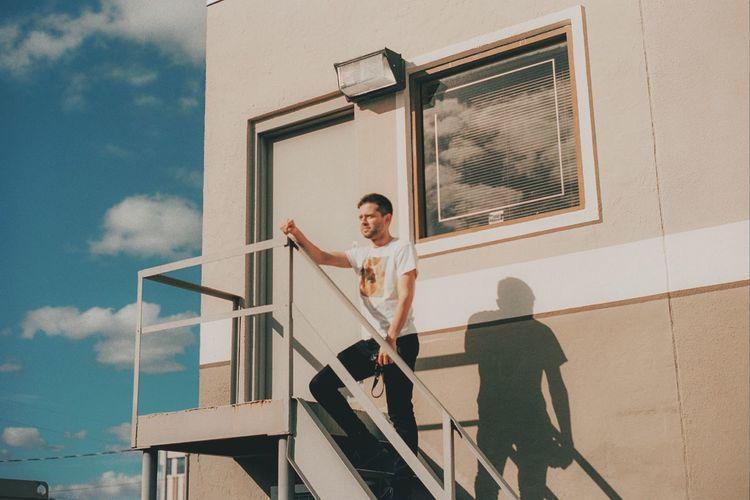 People standing by window against sky