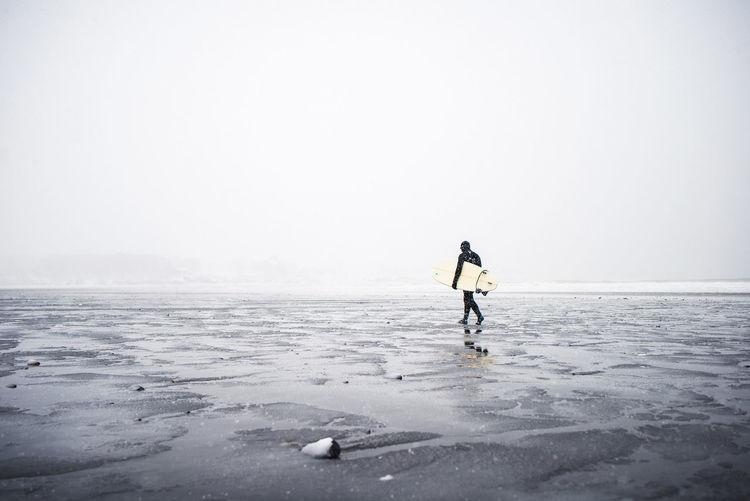 Man walking on frozen sea against clear sky