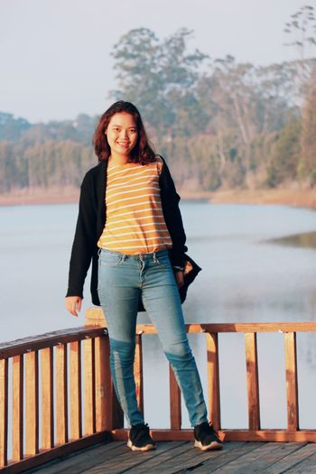 Portrait of smiling woman standing against railing