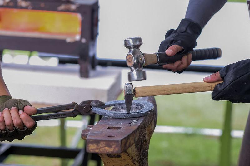 Close-up of men hammering metal at workshop