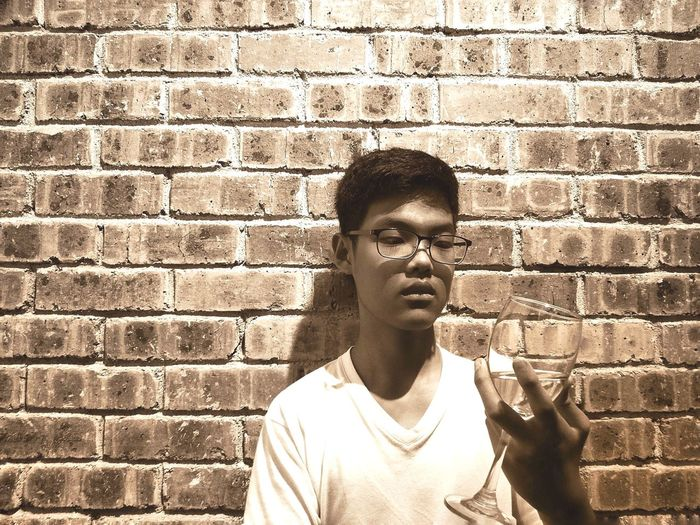 Young man holding wineglass against brick wall