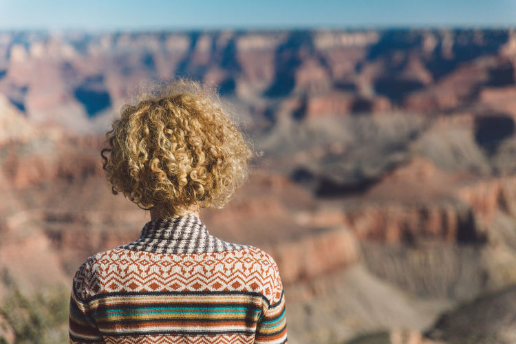Rear view of woman with curly hair against landscape at grand canyon national park