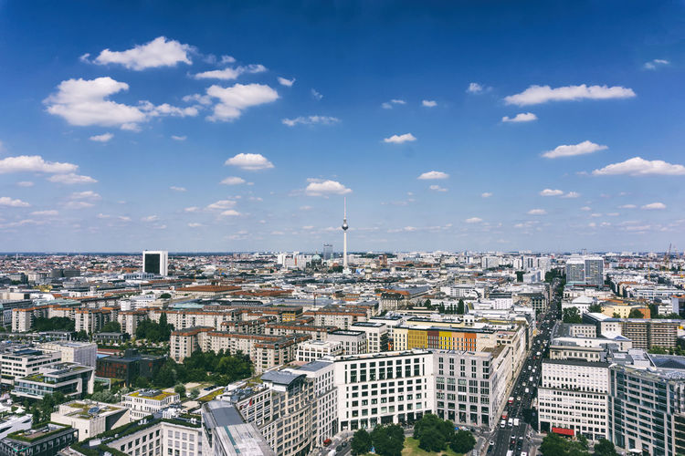 Aerial view of fernsehturm and cityscape against sky during sunny day