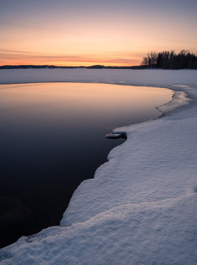Scenic winter landscape with lake reflections and sunset at evening in Finland Calm Finland Moment Of Silence Reflection Tranquility Travel Twilight Atmospheric Mood Beauty In Nature Cold Temperature Frozen Ice Idyllic Lake Melted Nature No People Scenics - Nature Snow Sunrise Sunset Tranquil Scene Tranquility Water Winter