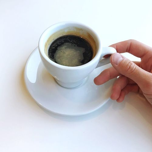 Cropped image of person holding coffee cup on table