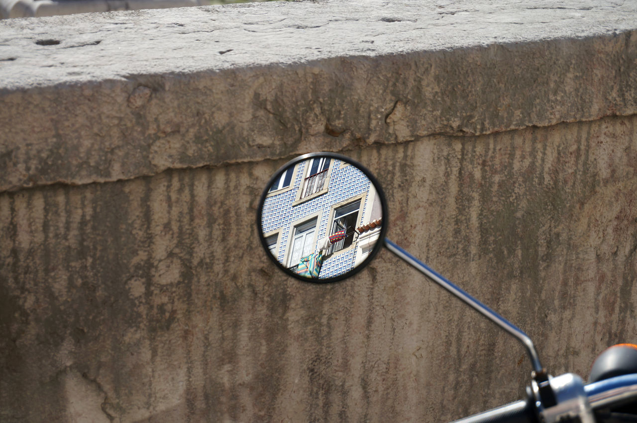 Reflection of building in motorcycle mirror