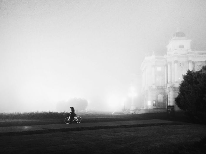 Person riding bicycle by building against sky during foggy weather