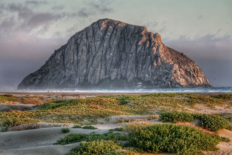 sunset at Morro Rock in Morro Bay, California Evening Atmosphere Dunescape Rock Formation Rock Hoodoo Water Spray Beachphotography California Pacific Ocean Pacific Pacific Coast Landscape_Collection Scenics Scenics - Nature Scenery Travel Destinations Tourist Attraction  Scenery Shots Sunset_collection Sunset Landscape Historic Landmark Morro Bay Morro Rock Water Sea Sky Landscape Grass Volcanic Landscape Volcanic Rock Geology