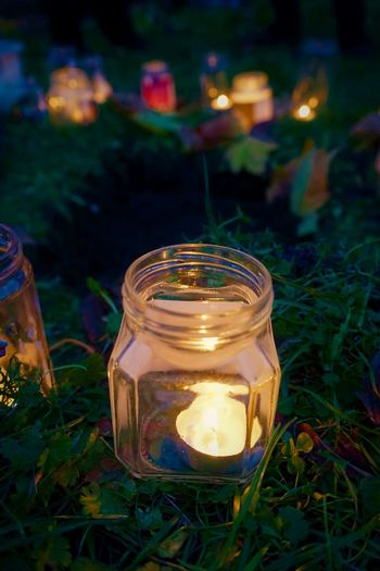 Candles at night oudoors Autumn Grass Light Burning Candle Candlelight Close-up Flame Funeral Glass Glass - Material Glowing Grass Ground Hole Illuminated Jar Lantern Leaves Night No People Outdoors Religious  Spirituality Tea Light