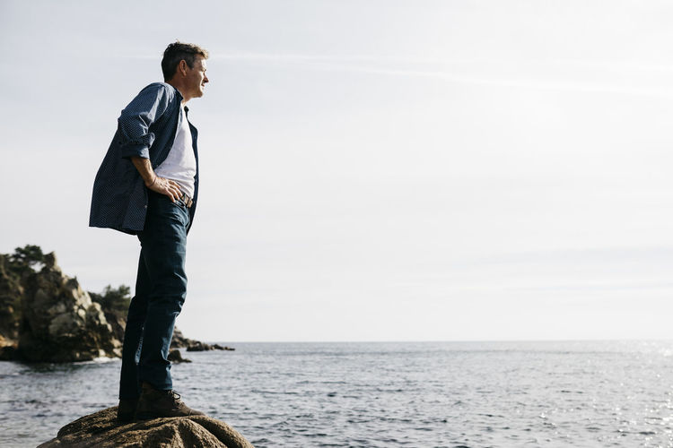 Man standing by sea against sky