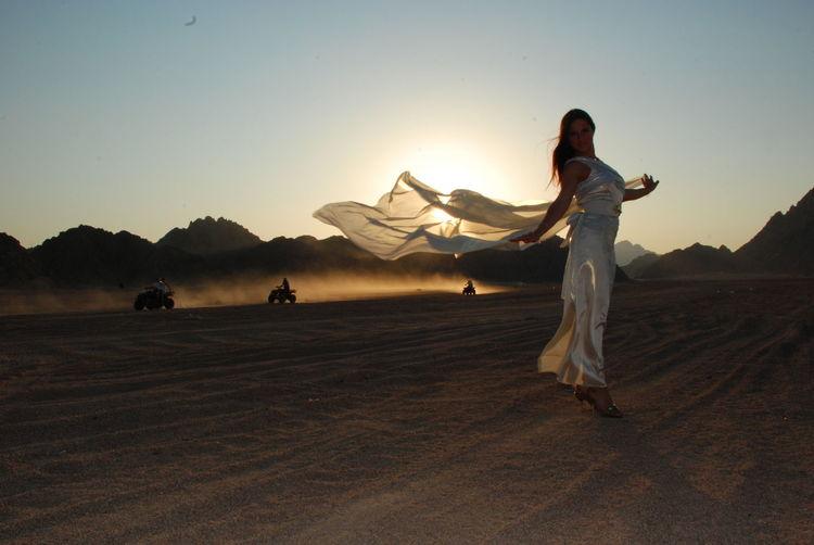 Full length of fashionable woman posing in desert during sunset