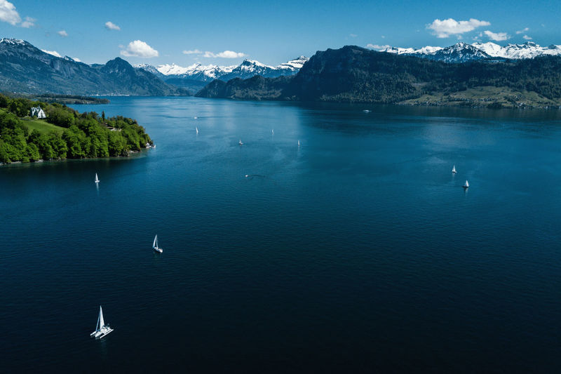 High angle view of sailboats in lake against mountains