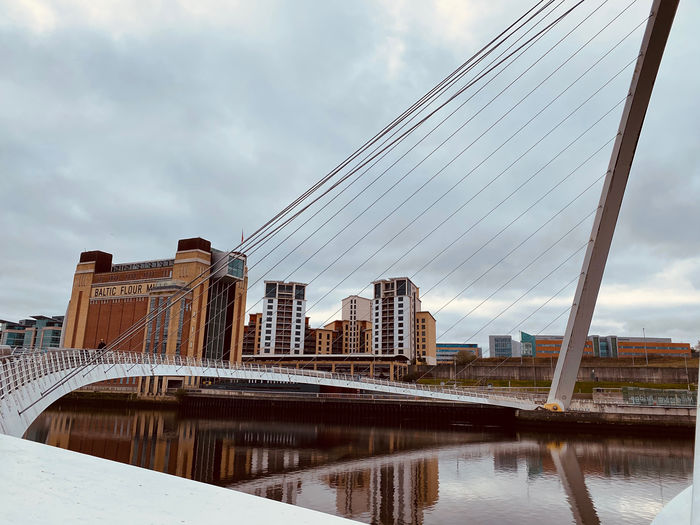 Reflection of suspension bridge in city against sky