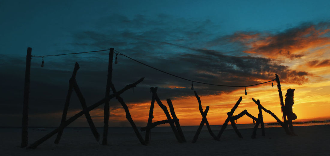 Silhouette woman standing by wooden posts at beach against sky during sunset