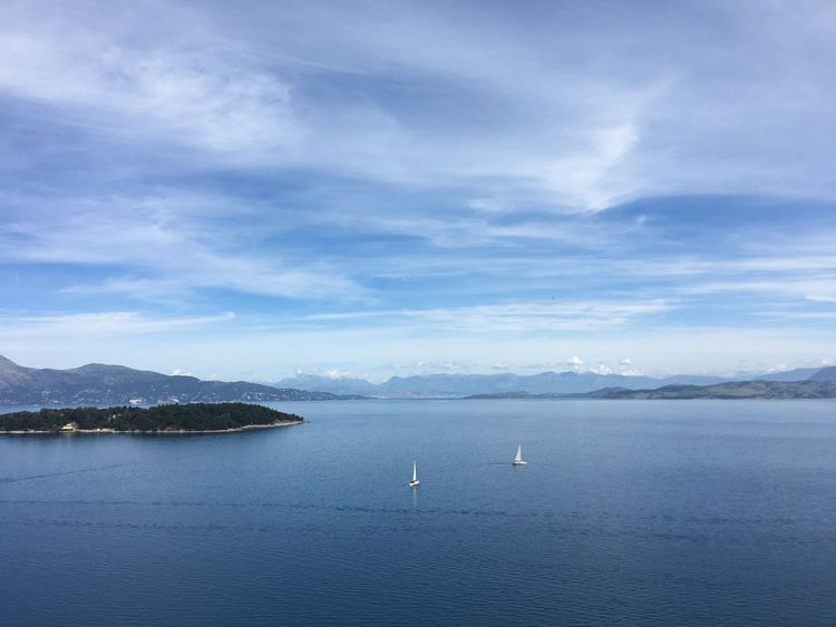 View of Vidos and Mainland Greece from Corfu Town Beauty In Nature Blue Calm On The Way Feel The Journey Coastline Corfu Town Day Green Idyllic Landscape Mountain Mountain Range Ocean Outdoors Remote Rippled Sailing Scenics Sky Tranquil Scene Tranquility Travel Destinations Water Yacht