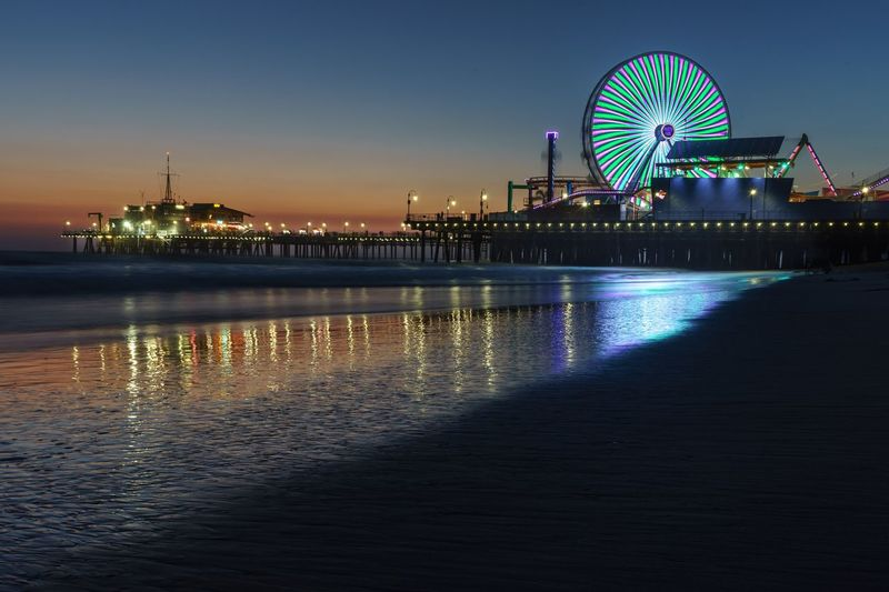 Illuminated Ferris Wheel By Beach At Night