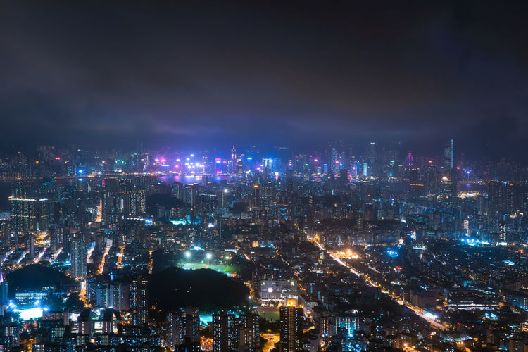 High angle view of illuminated city against sky at night