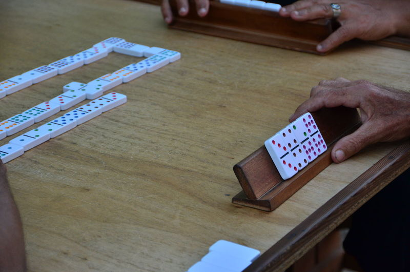 Cropped Image Of Hands Playing Domino At Table