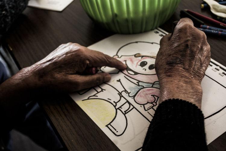 Senior Man Drawing On Paper
