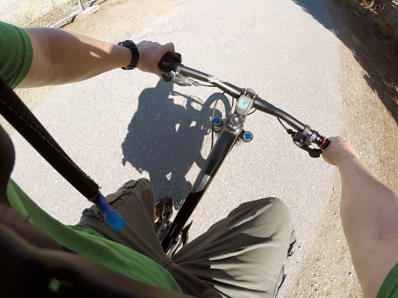 Low Section Of Man Riding Bicycle On Street During Sunny Day
