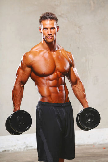 Portrait of shirtless macho young man lifting dumbbells against wall