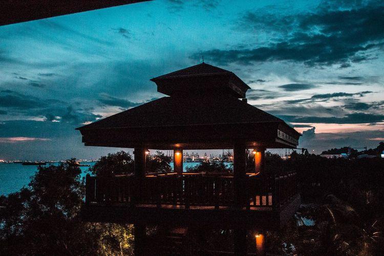 Illuminated house against sky at night