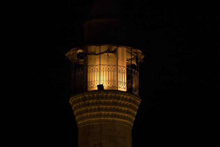Low angle view of illuminated tower against sky at night