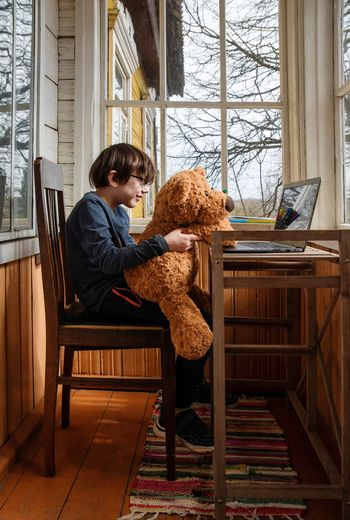 Kid sitting on chair, holding toy bear, looking at computer