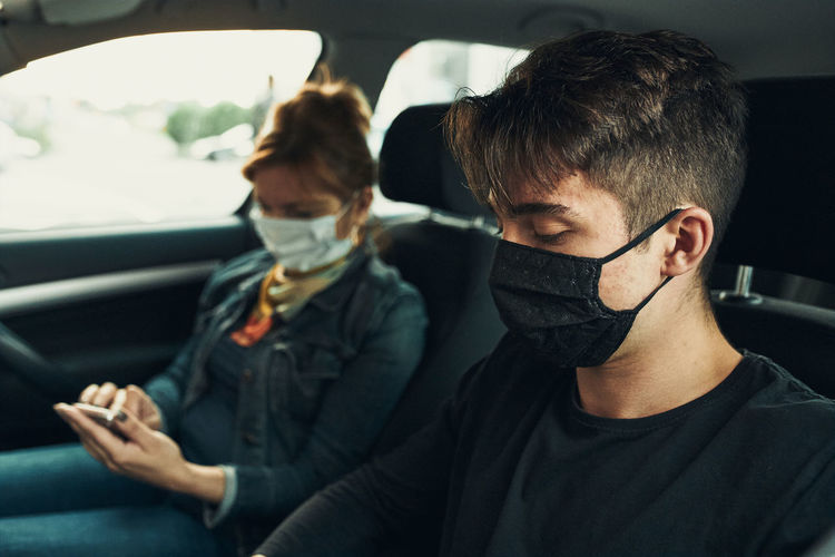 Young man and mature woman wearing mask sitting in car