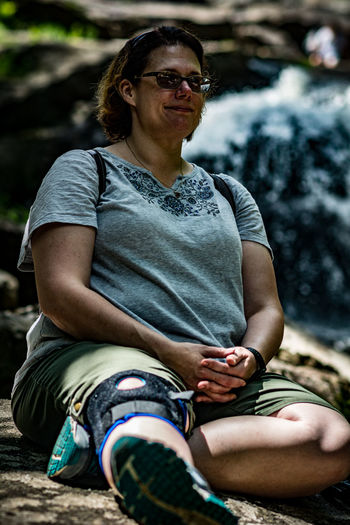 Mature Woman Looking Away While Relaxing On Rock