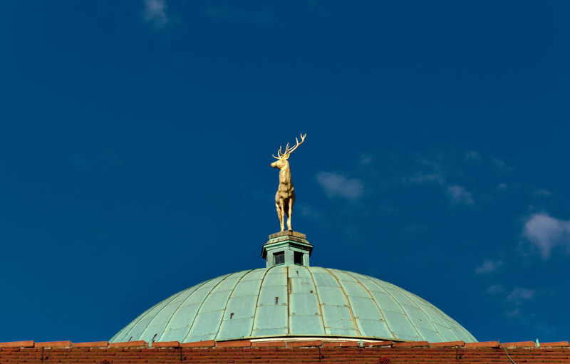 Low angle view of deer statue on dome against blue sky