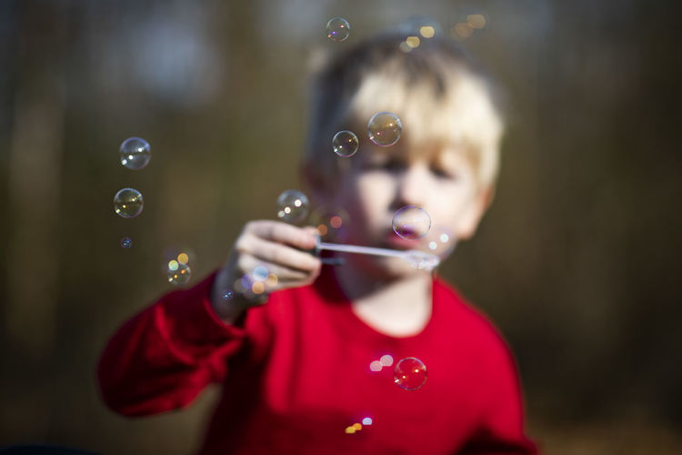 A five-year-old boy blows bubble in his yard. Childhood Child Offspring Bubble Bubble Wand Blowing One Person Front View Portrait Focus On Foreground Casual Clothing Holding Boys Males  Men Innocence Headshot Fragility Boy Summer Fall Playtime 5-year-old Illinois Blonde