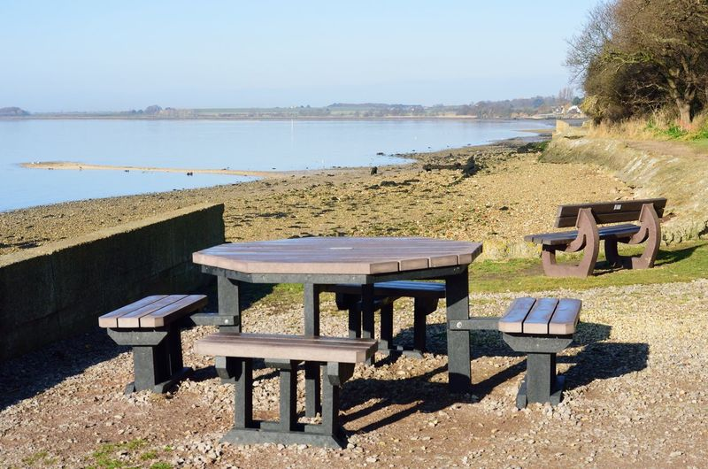 Empty coffee tables outside near coast with sun shining Seat Bench Nature Outdoor Tables Tables And Chairs Table And Chairs At The Sea Coffee Tranquil Scene
