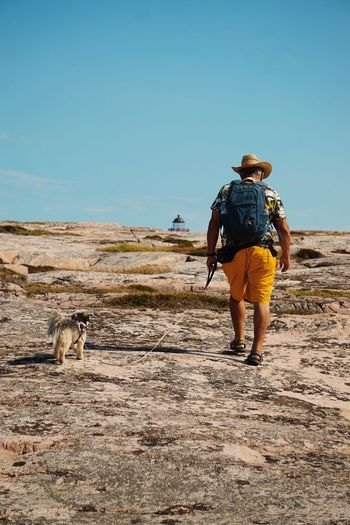 walking on the marble rocks of Hållö Dog Hiking Adventure Lighthouse Summer Travel Man Mature Men Sand Dune Full Length Desert Clear Sky Men Arid Climate Sand Walking Rear View Following Cowboy Cowboy Hat Arid Landscape Leading Backpack Hiker Hiking Pole