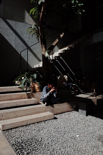 People sitting on staircase by building