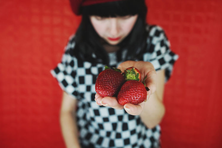 Close-up of woman holding strawberries