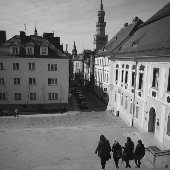 Rear View Of Friends On Steps Against Buildings