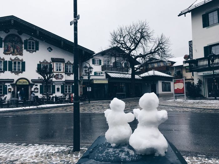 Snow on street by buildings against sky