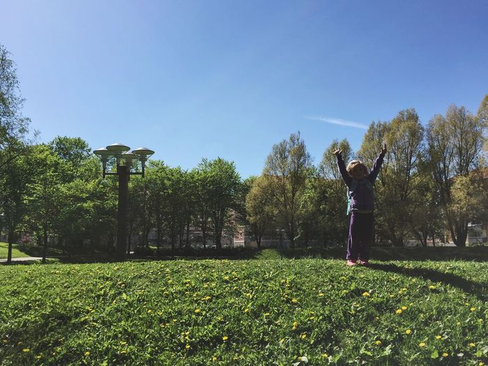 Full length of girl standing with arms raised at park against sky