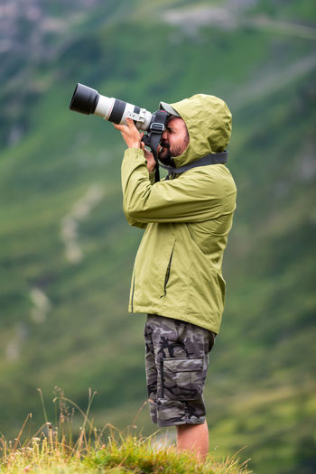 Photographer with telephoto lens in mountain landscape.