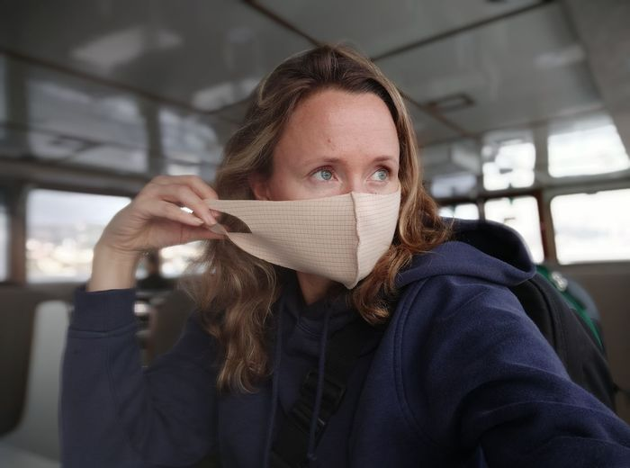 Woman wearing mask looking away while sitting in bus
